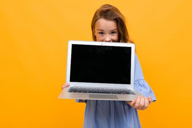 Urocza dziewczyna zagląda do laptopa z makietą na pomarańczowej ścianie