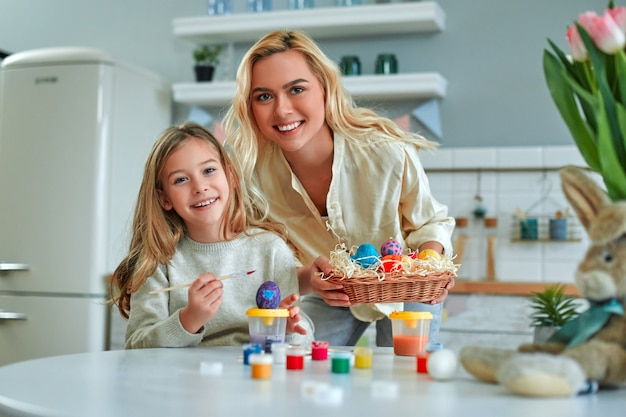 Urocza dziewczyna ze swoją piękną mamą przygotowuje się do świąt wielkanocnych i maluje jajka w swojej kuchni. matka i córka bawią się w kuchni.