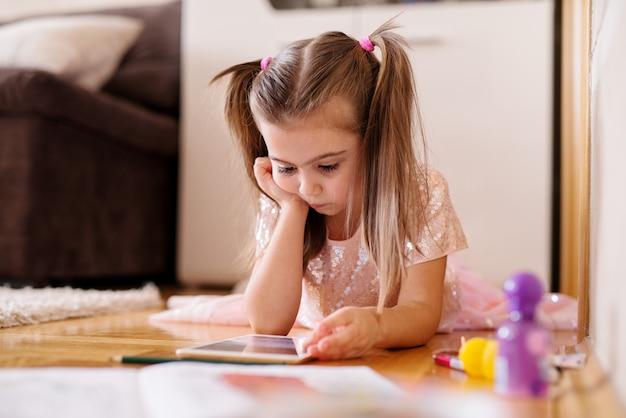 Urocza dziewczynka bawi się tabletem na podłodze.