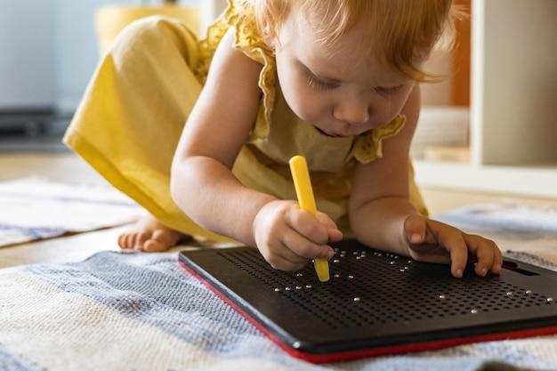 Urocza dziewczynka dziecinna tabletka magnetyczna z kulkami tworząca pikselową grafikę na plastikowej tablicy