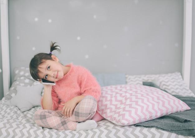 Urocza dziewczynka grająca w inteligentny telefon, smartfon ma negatywny wpływ na rozwój i zdrowie psychiczne dziecka