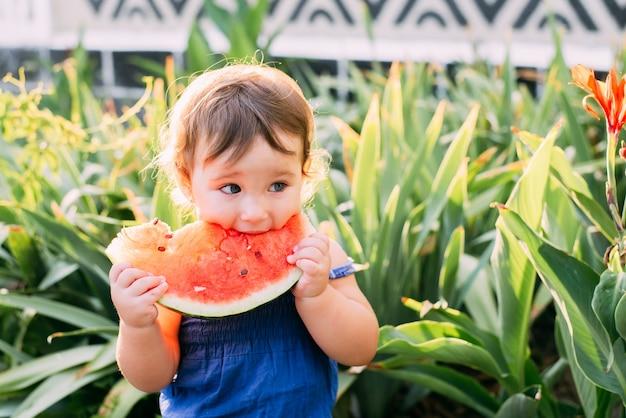 Urocza dziewczynka jedzenie arbuza na podwórku na tle roślin, bardzo słodkie