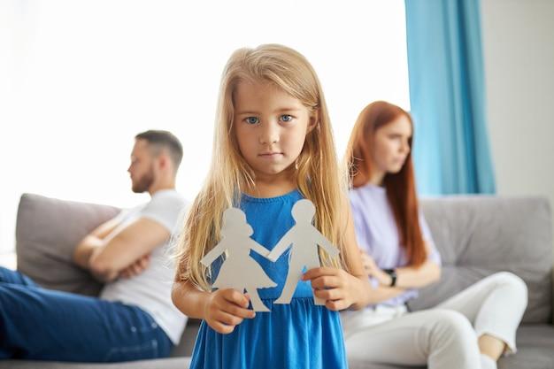 Urocza dziewczynka kaukaski między przygnębionymi rodzicami