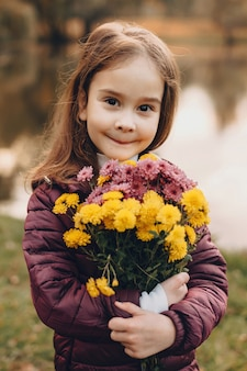 Urocza dziewczynka kaukaski patrząc na kamery i pozowanie z kwiatami z jeziorem na tle parku