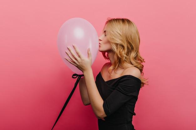 Urocza dziewczynka kaukaski z falowanymi włosami całuje balon helowy. spektakularna europejka w czarnym stroju bawiąca się na przyjęciu urodzinowym.