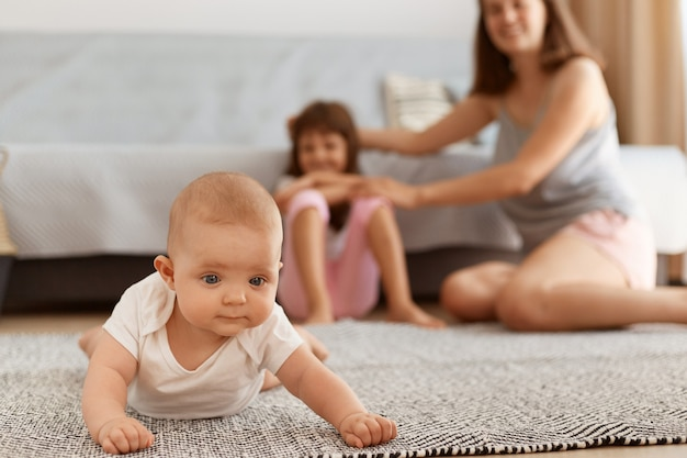 Urocza dziewczynka malucha czołgająca się na podłodze na dywanie w salonie, niemowlę dziewczynka bawiąca się w domu z matką i siostrą na tle, szczęśliwe dzieciństwo.