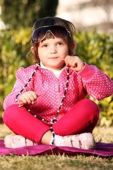 Urocza dziewczynka nakłada błyszczyk i bawi się naszyjnikiem mamy w parku