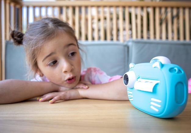 Urocza dziewczynka patrzy na niebieski zabawkowy aparat swoich dzieci, aby natychmiast wydrukować zdjęcia.