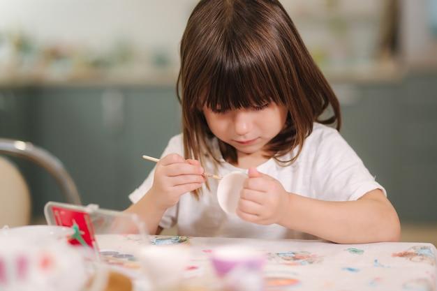 Urocza dziewczynka podczas drukowania pisanek w domu piękna dziewczyna przygotowuje się do świąt wielkanocnych