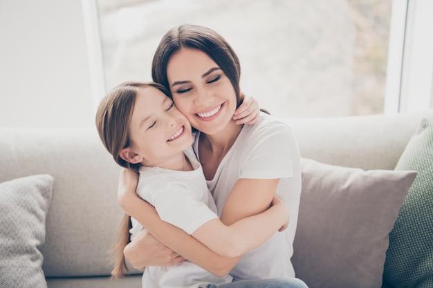Urocza dziewczynka przytula matkę na wygodnej kanapie w pokoju w pomieszczeniu