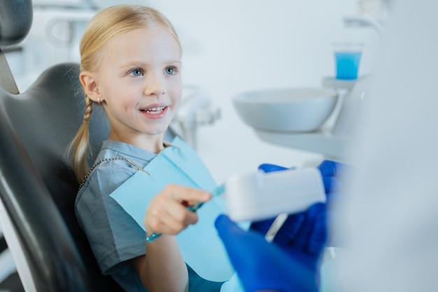 Urocza dziewczynka siedzi na fotelu dentystycznym i uczy się prawidłowego mycia zębów, ćwicząc na modelu dentystycznym