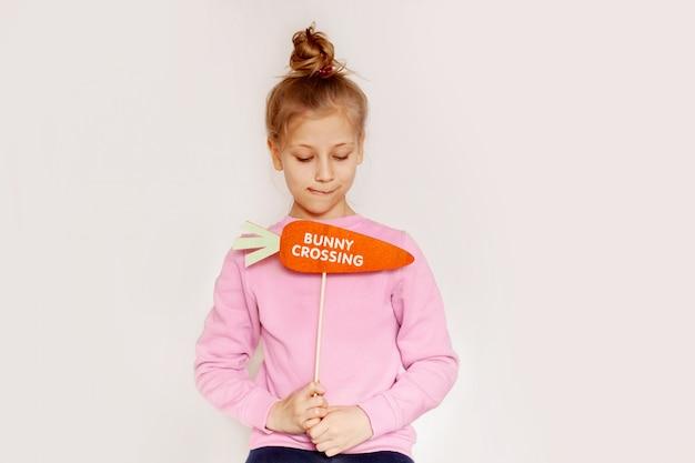 """Urocza dziewczynka trzyma marchewkę z napisem """"króliczek"""""""