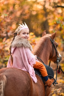 Urocza dziewczynka ubrana jak księżniczka jeździ konno po lesie jesienią