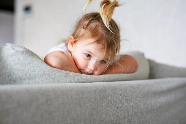 Urocza dziewczynka w białej słonecznej sypialni. noworodek relaksujący na niebieskim łóżku. żłobek dla małych dzieci. noworodek w czasie brzucha z zabawkami w oknie.