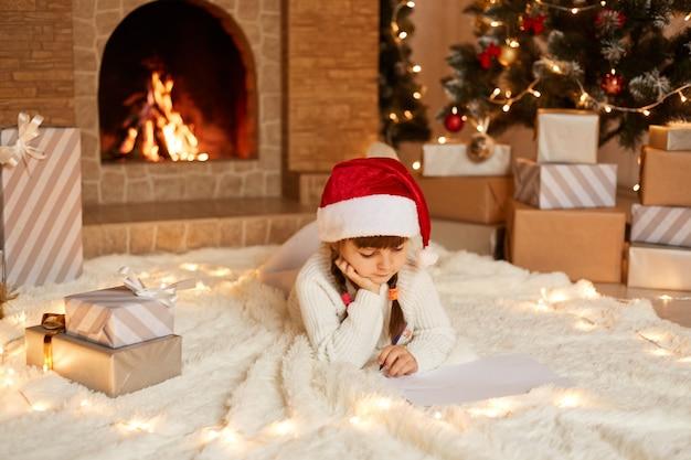 Urocza dziewczynka w białym swetrze i czapce świętego mikołaja, leżąca na podłodze przy choince, z pudełkami prezentowymi i kominkiem, pisząca list do świętego mikołaja.