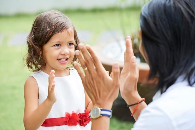 Urocza dziewczynka w bufiastej sukience klaszcząca w dłonie z ojcem, gdy bawią się na świeżym powietrzu