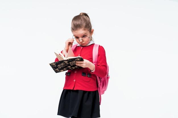 Urocza dziewczynka w czerwonej szkolnej kurtce, czarnej sukience, plecaku i zaokrąglonych okularach