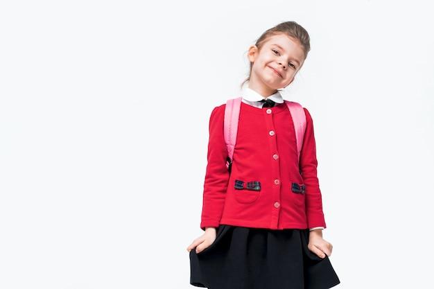 Urocza dziewczynka w czerwonej szkolnej kurtce, czarnej sukience, plecaku nieśmiało przylega do spódnicy i uśmiecha się