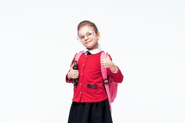 Urocza dziewczynka w czerwonej szkolnej kurtce, czarnej sukience, zaokrąglonych okularach i plecaku pokazującym kciuk do góry