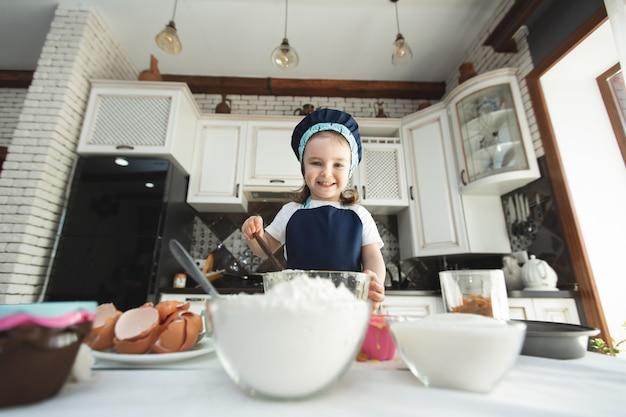 Urocza dziewczynka w fartuchu i czapce szefa kuchni miesza ciasto drewnianą szpatułką