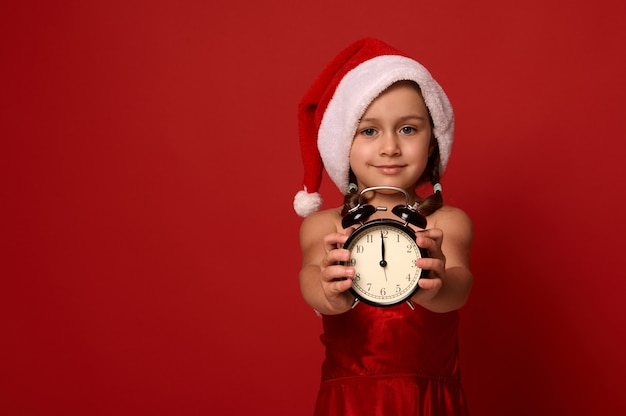 Urocza dziewczynka w kapeluszu i kostiumie świętego mikołaja pokazuje północ na zegarze z budzikiem, uśmiecha się, patrząc na kamerę i pozowanie na czerwonym tle z miejsca na kopię. szczęśliwego nowego roku, wesołych świąt