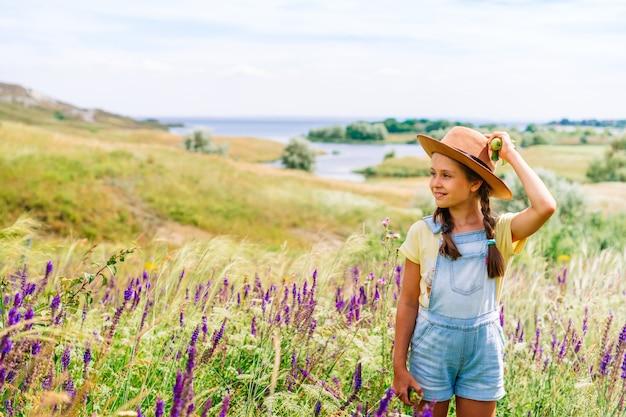 Urocza dziewczynka w kapeluszu, trzymając w ręku jabłka na tle malowniczego pagórkowatego krajobrazu
