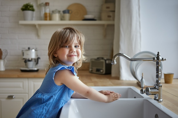 Urocza dziewczynka w niebieskiej sukience mycia rąk w kuchni. słodkie dziecko kobiece patrząc i uśmiecha się do kamery, pomaga matce, zmywa naczynia, stojąc przy zlewie. dzieci, dzieciństwo, gotowanie i prace domowe