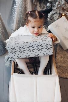 Urocza dziewczynka w prezenty świąteczne. pokój urządzony na boże narodzenie.