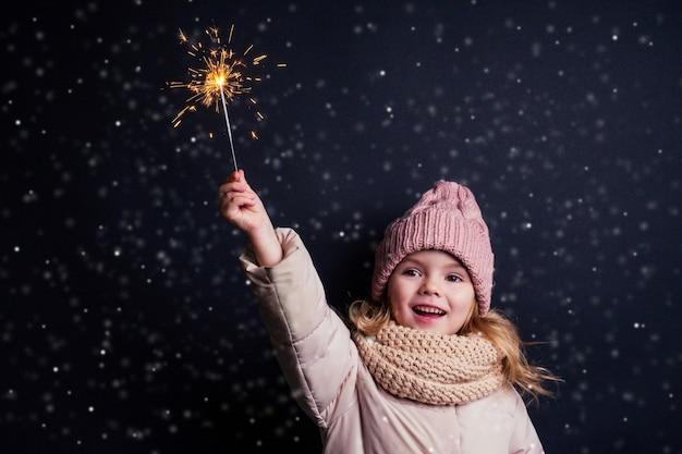 Urocza dziewczynka w różowym kapeluszu z dzianiny, trzymając fajerwerki na czarnym tle w studio. słodkie blond dziecko z boże narodzenie marzenie. szczęśliwe dziecko cieszyć się iskrami ognia. sylwester święta bożego narodzenia życzę.