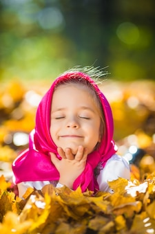 Urocza dziewczynka w różowym szaliku i sukience, białej kurtce jak masza i niedźwiedź z kreskówki.