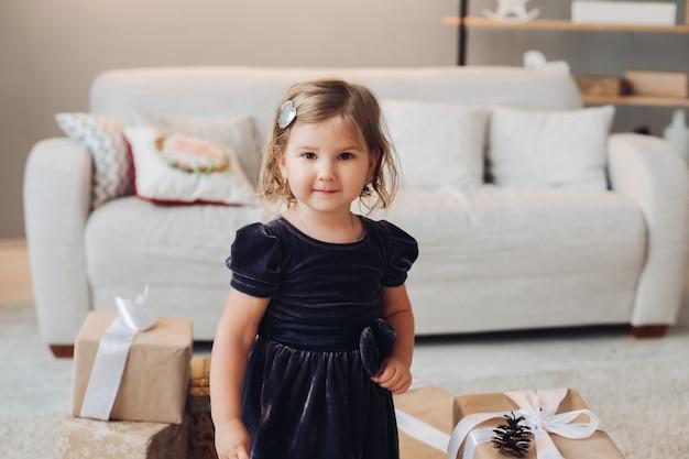 Urocza dziewczynka w sukience siedzi otoczona wieloma pudełkami świątecznych prezentów i chce je otworzyć