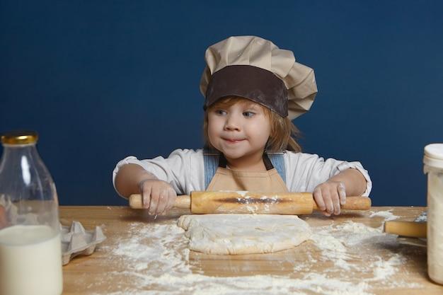 Urocza dziewczynka wydymająca usta tajemniczym spojrzeniem podczas samodzielnego wałkowania ciasta