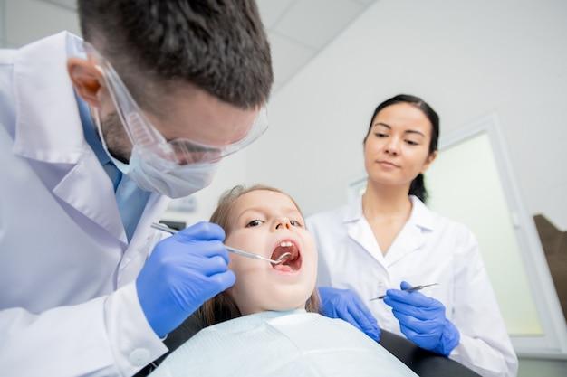 Urocza dziewczynka z otwartymi ustami siedzi w fotelu w klinikach stomatologicznych podczas badania jamy ustnej z lustrem przez dentystę