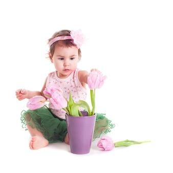 Urocza dziewczynka z różowymi tulipanami, na białym tle