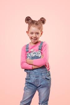Urocza dziewczynka z uroczymi bułeczkami do włosów na sobie różową koszulę i dżinsowy kombinezon, uśmiechnięta i wyglądająca