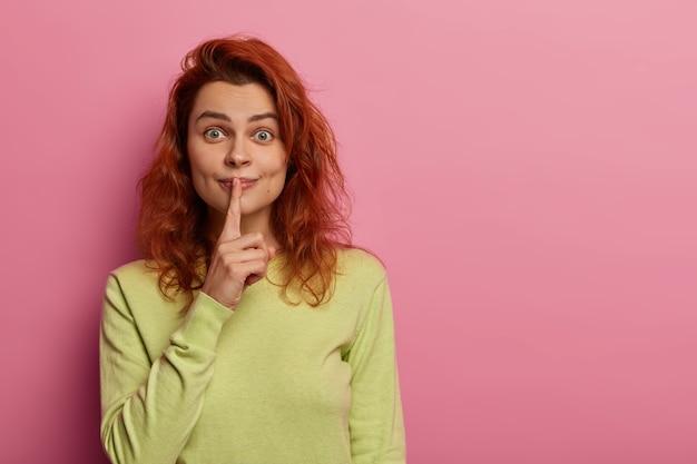 Urocza entuzjastyczna kobieta z czerwonymi falującymi włosami, plotkuje i prosi o nie rozpowszechnianie plotek, trzyma palec wskazujący na ustach