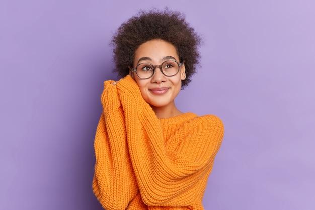 Urocza etniczna dziewczyna z naturalnymi włosami afro trzyma ręce blisko twarzy i wygląda z rozmarzonym wyrazem gdzieś, nosi luźny pomarańczowy sweter z dzianiny.