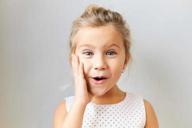 Urocza europejska dziewczyna w wieku przedszkolnym pozująca odizolowana z ręką na policzku, mówiąca wow z otwartymi ustami, zdumiona ekscytującymi wiadomościami, wyrażająca prawdziwą reakcję, ubrana w sukienkę w kropki