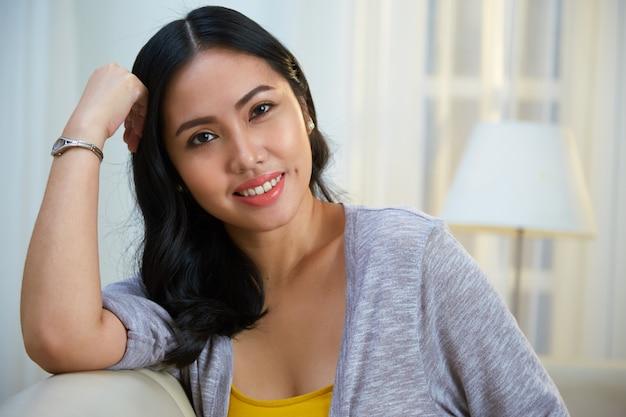 Urocza filipińska kobieta opiera na kanapie z powrotem
