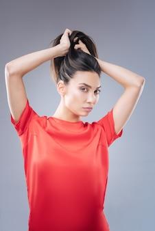 Urocza fryzura. modna młoda piękna kobieta stojąca przed lustrem i próbująca zrobić ładny kucyk