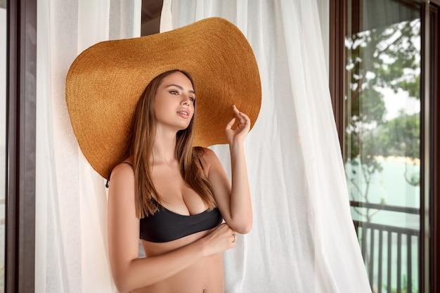 Urocza i atrakcyjna kobieta z makijażem pozuje w dużym słomkowym kapeluszu przed oknem