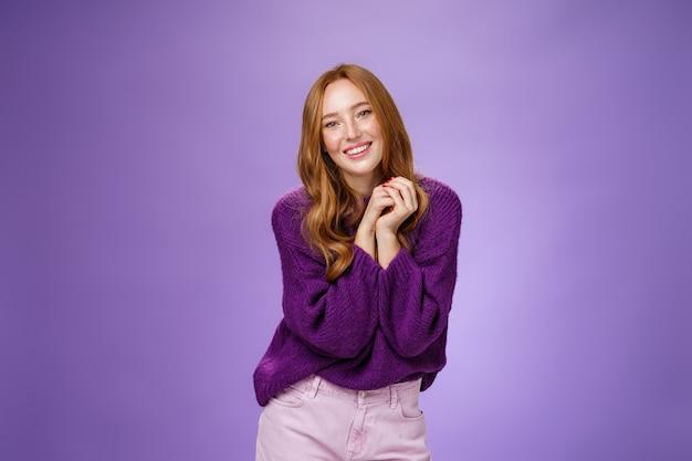 Urocza i delikatna, beztroska rudowłosa dziewczyna z uroczymi piegami trzymającymi się za ręce blisko ramion, pozująca zalotnie i kobieco uśmiechnięta szeroko, mająca pozytywne, szczęśliwe nastawienie nad fioletową ścianą.