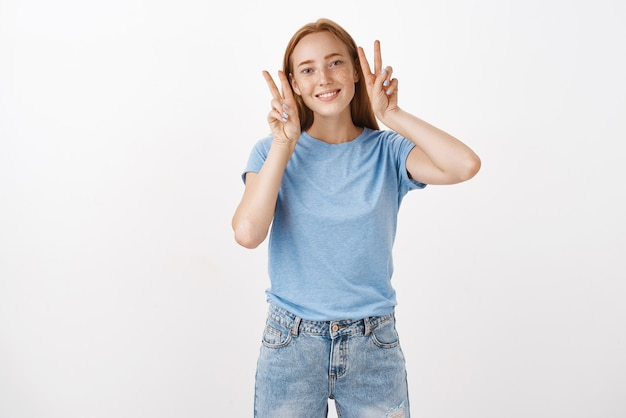 Urocza i delikatna kobieca ruda kobieta w niebieskiej koszulce pokazująca znaki zwycięstwa lub pokoju przy twarzy i uśmiechająca się radośnie pozująca, robiąca zdjęcie do sieci społecznościowej, aby wysłać przyjaciół