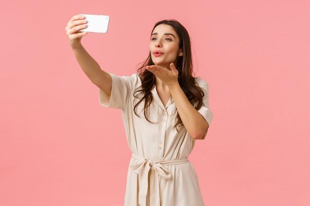 Urocza i delikatna, kusząca brunetka w sukience trzyma telefon, bierze selfie i całuje w telefonie komórkowym, transmituje wideo na żywo na blogu, fotografuje na różowej ścianie