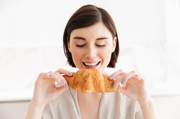 Urocza i głodna kobieta w szlafroku zjada śniadanie w mieszkaniu, jedząc smaczne rogaliki z przyjemnością