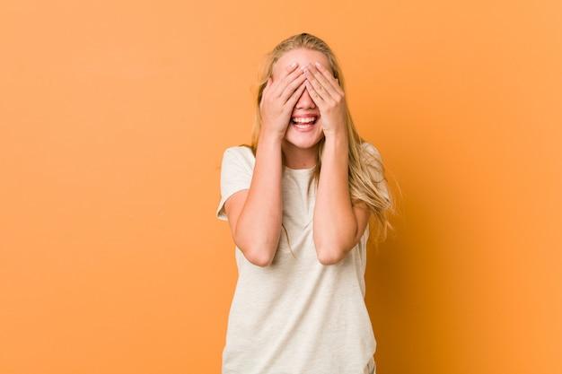 Urocza i naturalna nastolatka zakrywa oczy dłońmi, uśmiecha się szeroko, czekając na niespodziankę.