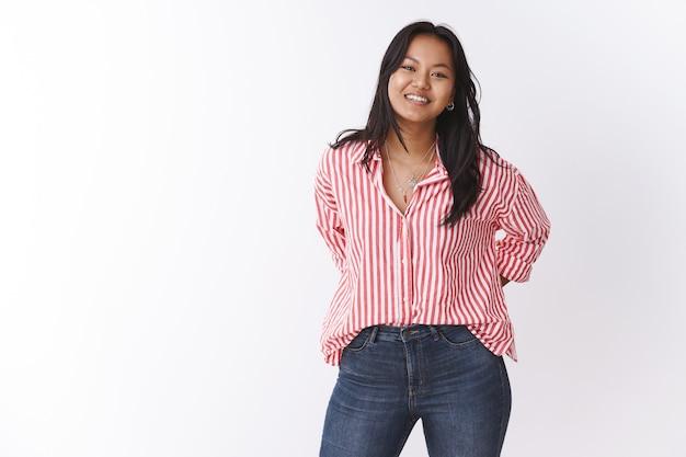 Urocza i przyjemna pracownica biurowa słuchająca prośby przyjaciela na lunch, trzymająca się za ręce na plecach i uśmiechnięta słodko przed kamerą, czując się szczęśliwa i radosna, pozując zrelaksowana na białej ścianie