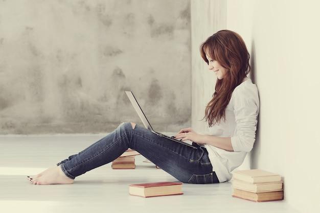 Urocza i urocza dorosła kobieta z laptopem i książkami