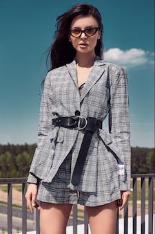 Urocza jasna brunetka ubrana w wełniany kraciasty garnitur