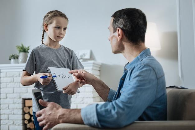 Urocza jasnowłosa dziewczynka trzymająca zeszyt i stojąca obok taty i prosząca go o pomoc w matematyce, a on wskazujący na jej równanie matematyczne